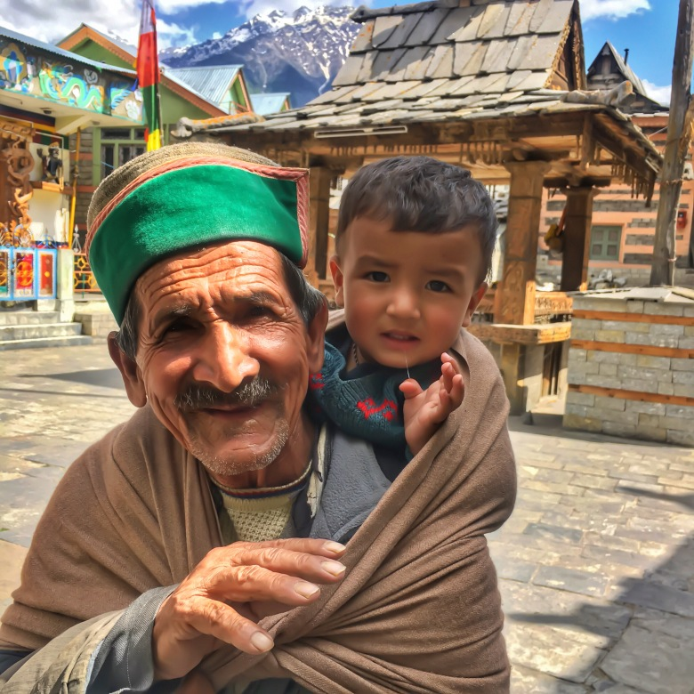 a kid and his grandfather in sangla valley, india